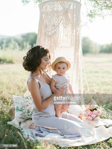 mother and little daughter playing together in a park. a nice girl and her mother enjoy summertime. family playing under macrame cotton canopy on blanket with pillows. - família monoparental imagens e fotografias de stock
