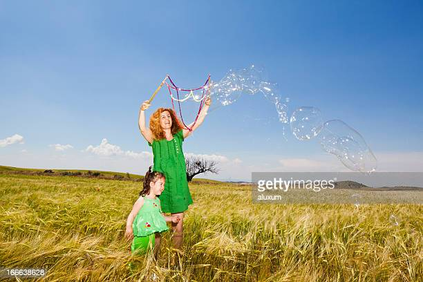 Mother and little daughter playing with soap bubbles