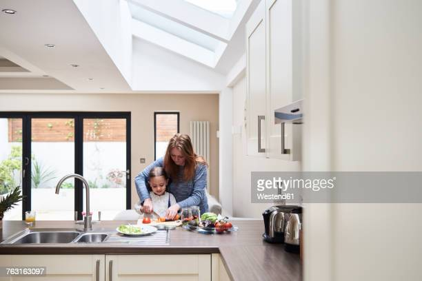 Mother and little daughter preparing food together in the kitchen