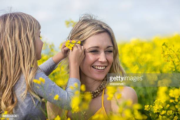 Mother and little daughter together in rape field