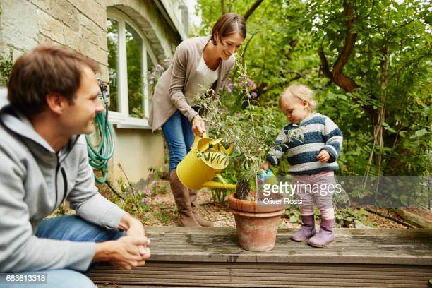 Mother and little daughter watering plant on terrace