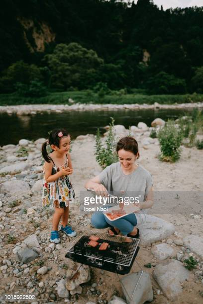 Mother and little girl having BBQ by river, Niigata, Japan