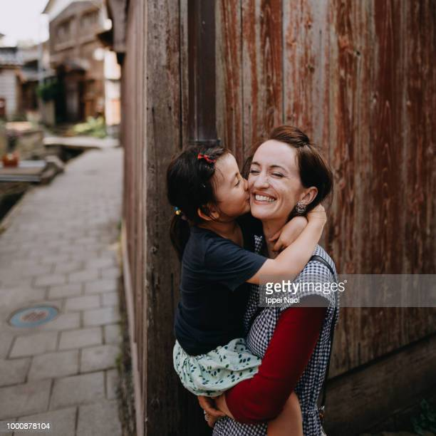 Mother and little girl having intimate moment in old Japanese village
