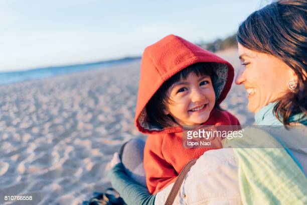 Mother and little girl having intimate moment on winter beach