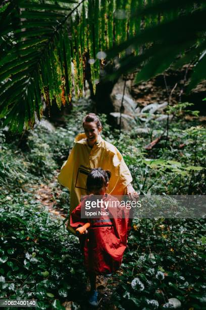 Mother and little girl hiking in rainy jungle, Okinawa, Japan