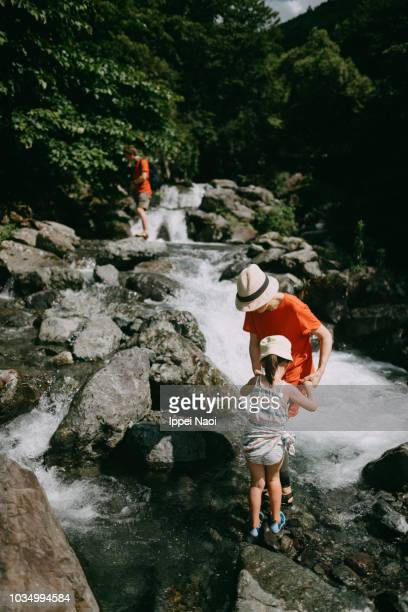 Mother and little girl holding hands and hiking up river in mountain