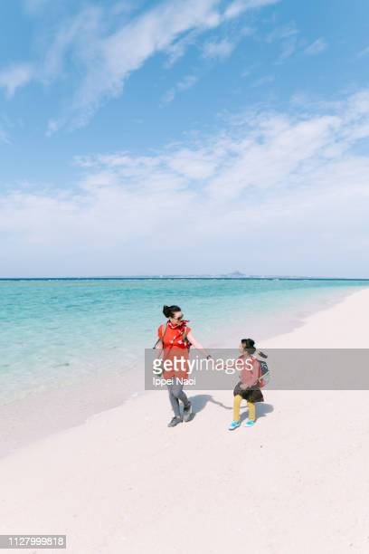 Mother and little girl looking at each other and walking on tropical beach, Okinawa, Japan