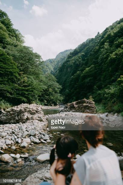 Mother and little girl looking at river and mountains, Japan