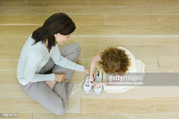 Mother and little girl sitting on floor, girl learning to tie shoe laces, view from directly above