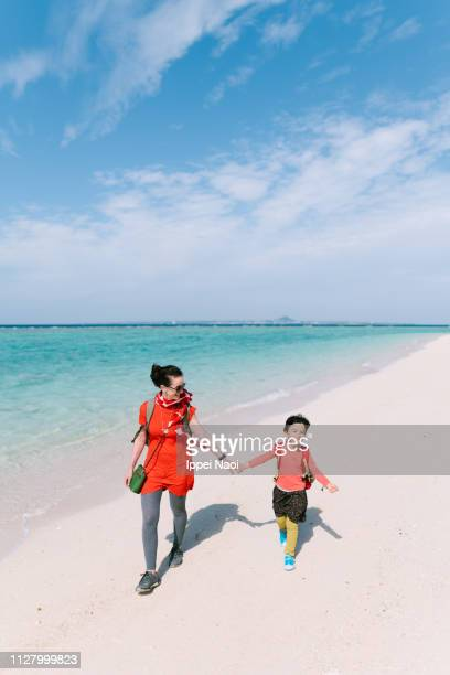 Mother and little girl walking together on tropical beach, Okinawa, Japan