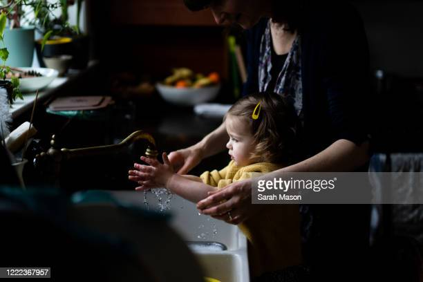 mother and little girl washing hands - england stock pictures, royalty-free photos & images