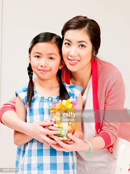 Mother and Little Girl with Easter Eggs in a Jar