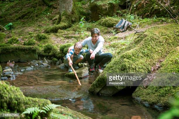 Mother and little son crouching at edge of a brook
