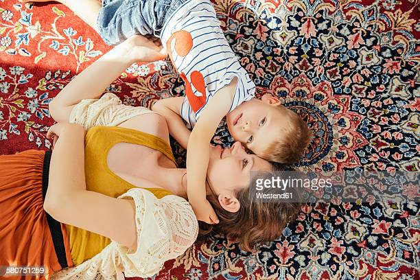 mother and little son cuddling on a persian rug at home - persian rug stock photos and pictures