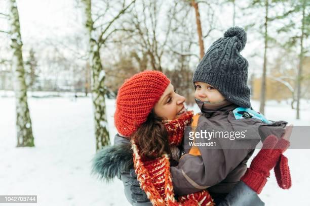 mother and little son in the snow - kopfbedeckung stock-fotos und bilder