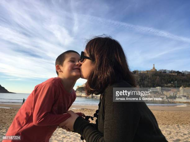 Mother and little son kissing in La Concha beach at sunset. Donostia-San Sebastian, Basque Country