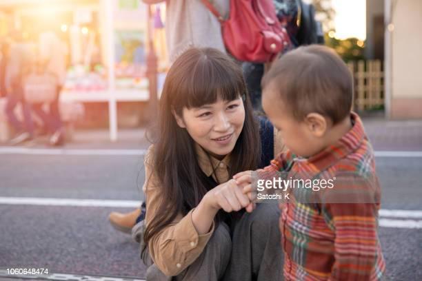 母と幼い息子の路上手で遊んで