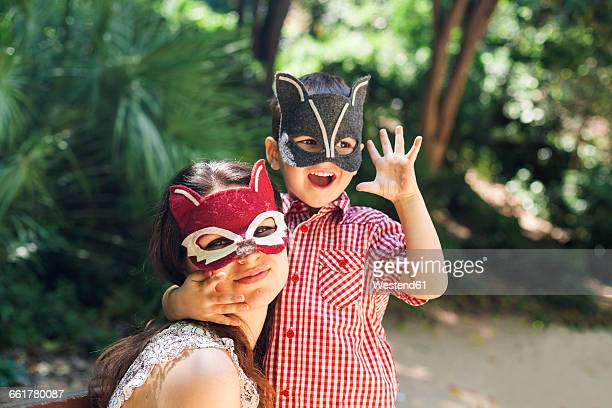 Mother and little son with animal masks playing in the park