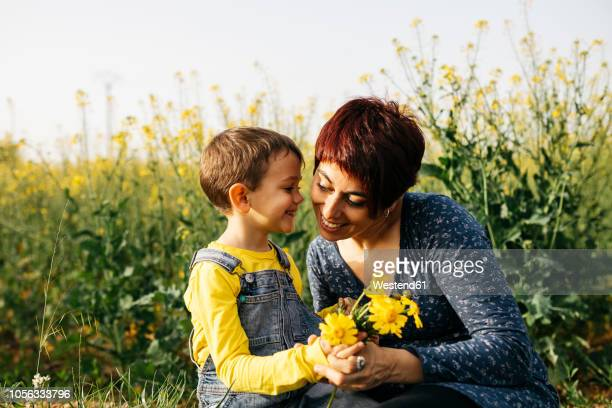Mother and little son with picked flowers in a field