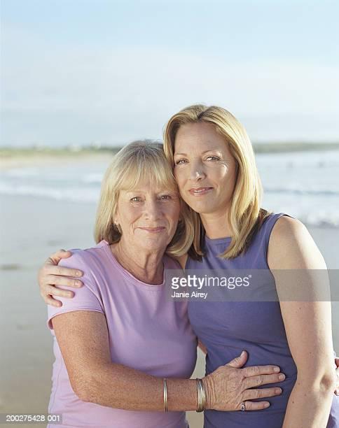 mother and mature daughter embracing on beach, smiling, portrait - vestido roxo - fotografias e filmes do acervo