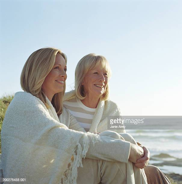 Mother and mature daughter sitting by ocean, smiling
