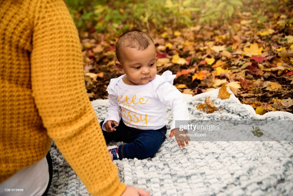 Mother and mixed-race baby girl enjoying autumn in urban park. : Stock Photo