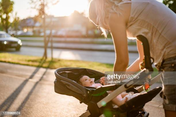 mother and newborn baby on sunset - baby stroller stock pictures, royalty-free photos & images