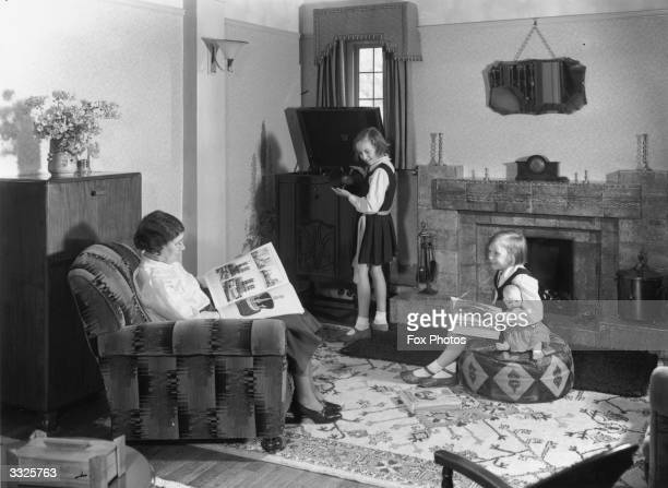 A mother and one of her young daughters sit reading in a sittingroom while another daughter wearing a gym slip changes a gramophone record