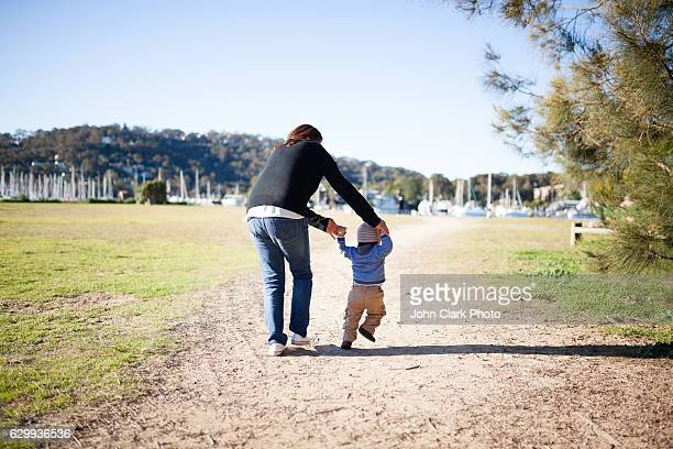 Mother and one year old son walking in park 1