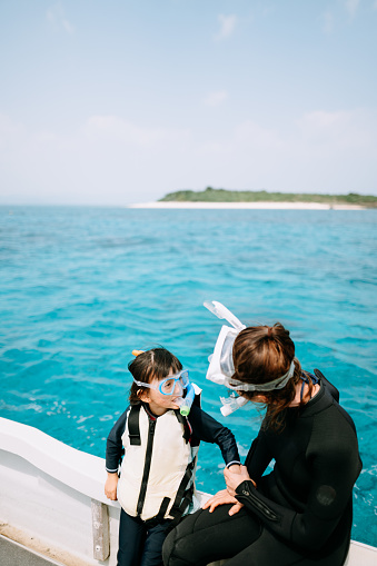 Mother and preschool child with snorkel mask, looking at each other on boat, Okinawa, Japan - gettyimageskorea