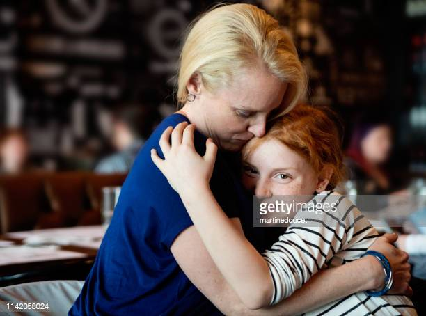 Mother and preteen daughter cuddling at a restaurant table.