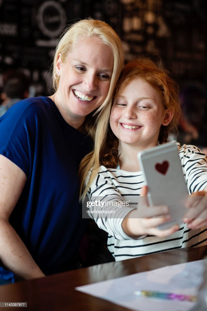 Mother and preteen daughter doing selfies at a restaurant table. : Stock Photo