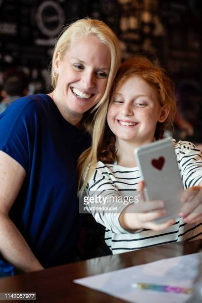 Mother and preteen daughter doing selfies at a restaurant table.