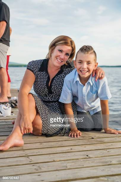 """mother and pre-teen son sitting on a pier at sunset. - """"martine doucet"""" or martinedoucet foto e immagini stock"""