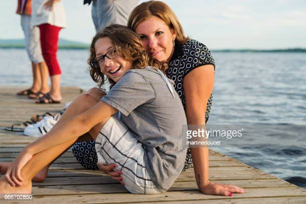 """mother and pre-teen son sitting on a pier at sunset. - """"martine doucet"""" or martinedoucet stock pictures, royalty-free photos & images"""
