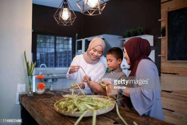 mère et soeur avec le frère faisant la nourriture - eid al adha photos et images de collection