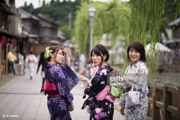 Mother and sisters in Yukata walking in traditional edo-period style town