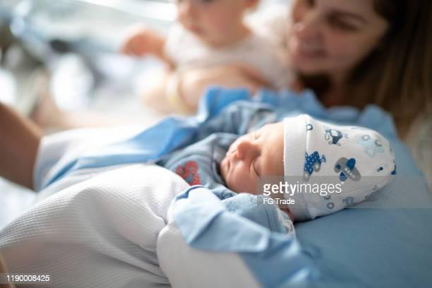 moeder en slapende pasgeboren en zoon in ziekenhuis - menselijke vruchtbaarheid stockfoto's en -beelden