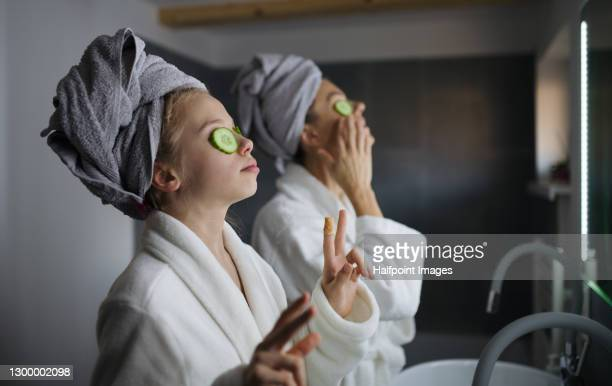 mother and small daughter indoors in bathroom at home, putting cucumbers on eyes. - body care stock pictures, royalty-free photos & images
