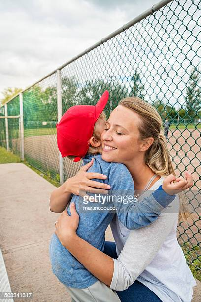 mother and small son hugging near baseball field. - baseball mom stock pictures, royalty-free photos & images