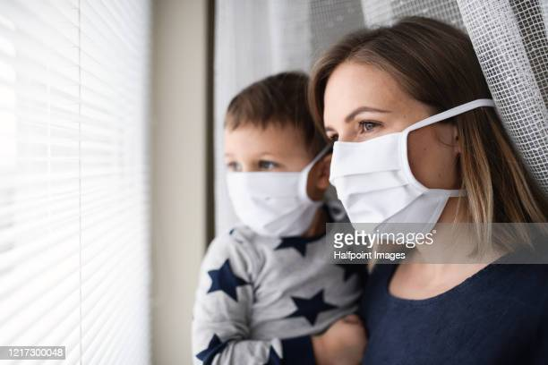mother and small son with face mask indoors at home, quarantine concept. - single mother stock pictures, royalty-free photos & images