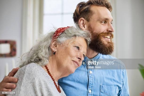 mother and smiling adult son - sohn stock-fotos und bilder