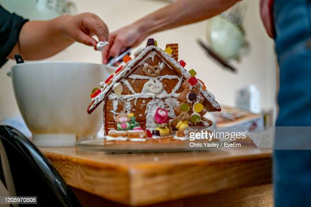 mother and son adding the final elements to a homemade and decorated christmas ginger bread house - home made stock pictures, royalty-free photos & images
