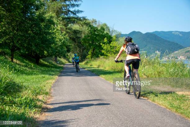 mother and son are cycling  by the danube river, wachau, austria - bicycle lane stock pictures, royalty-free photos & images