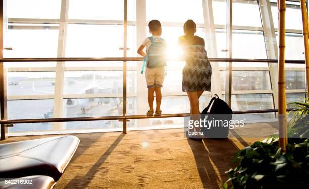 Mère et fils à l'aéroport en attente de départ