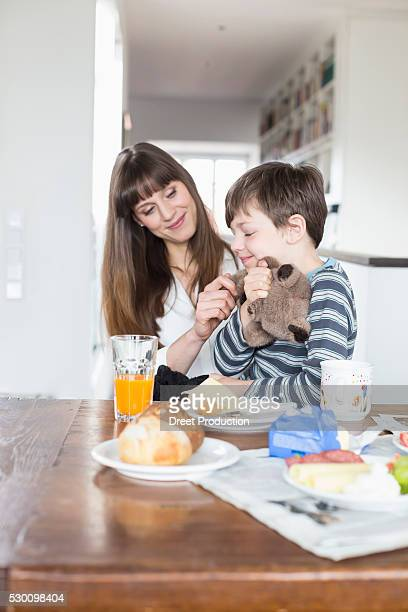 Mother and son at breakfast table, smiling