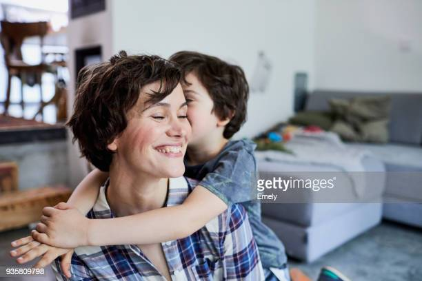 mother and son at home, son hugging mother - kindheit stock-fotos und bilder