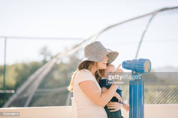 mother and son at playground, looking through telescope - heshphoto stock pictures, royalty-free photos & images