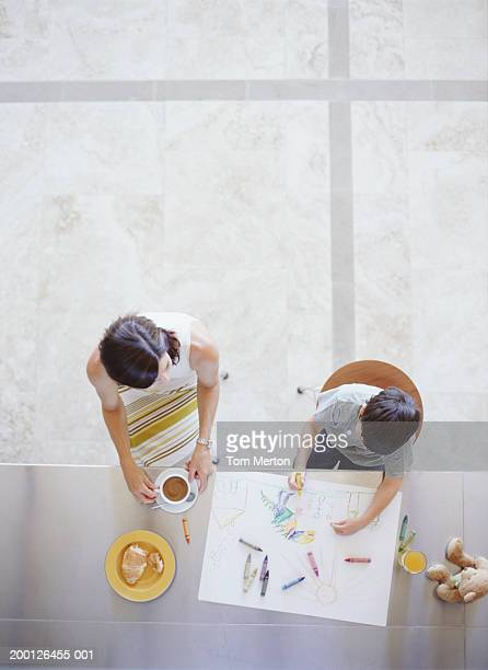 Mother and son (4-6) at table, boy drawing, overhead view