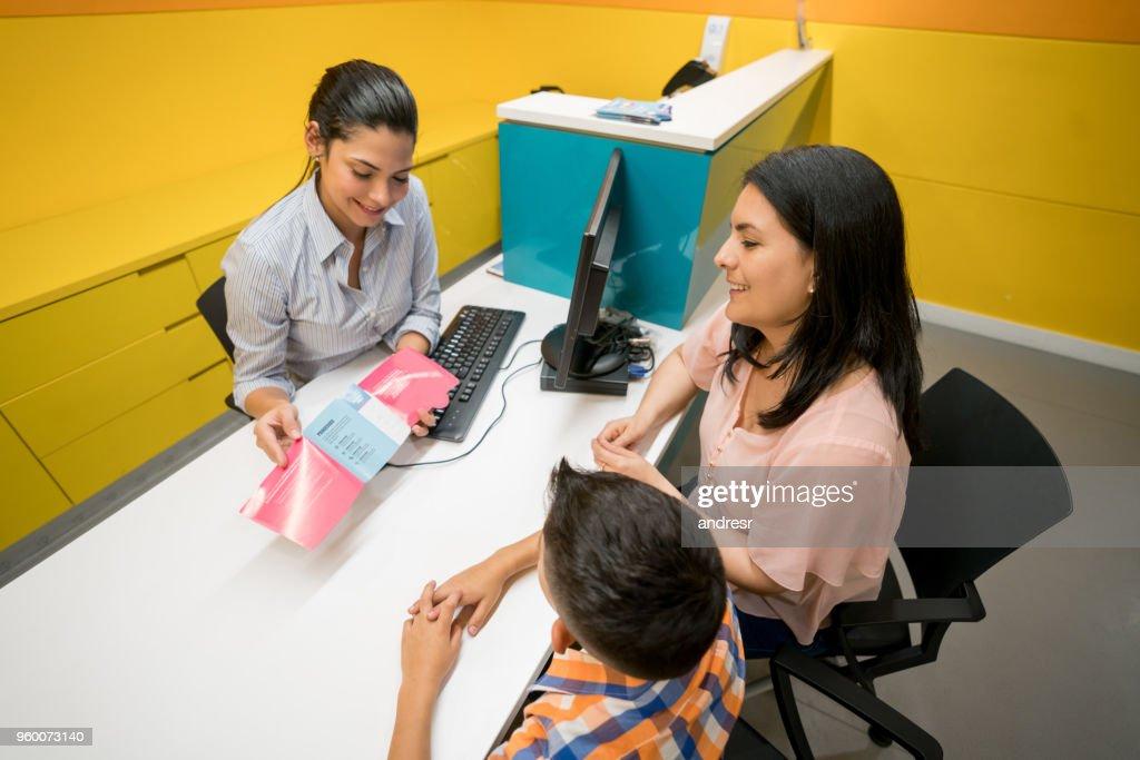 Mutter und Sohn an der Rezeption der Klinik Abrufen von Informationen über ein Verfahren und freundliche Assistentin zeigt ihnen eine Broschüre : Stock-Foto